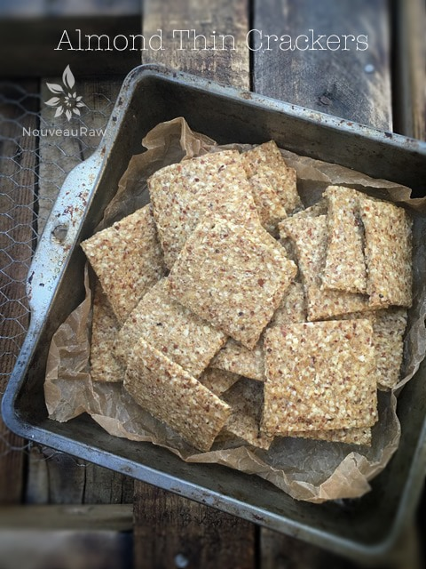 raw gluten free Almond Thin Crackers displayed on a wooden barn wood table