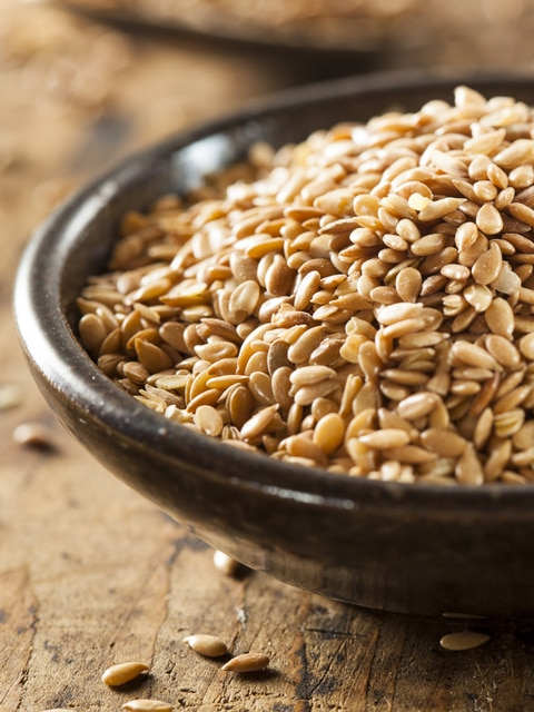 closeup flax seeds in a wooden bowl