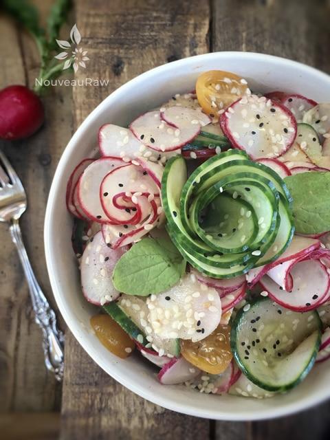 a close up of raw vegan fresh Radish, Cucumber, Apple Salad served in a white bowl