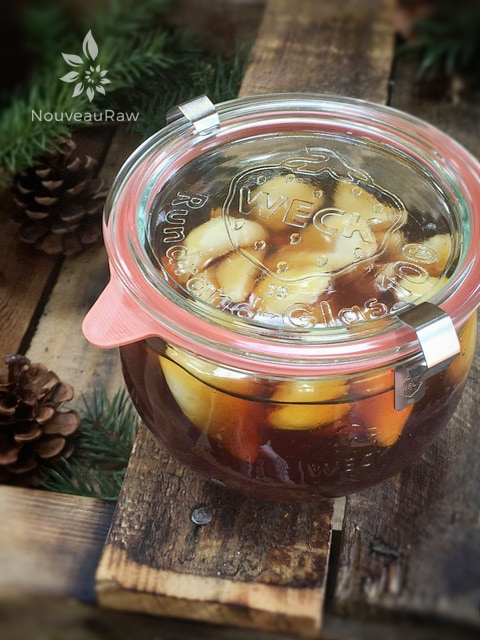 a close up of raw vegan Garlic Honey Throat, Cold and Flu Remedy displayed on barn wood