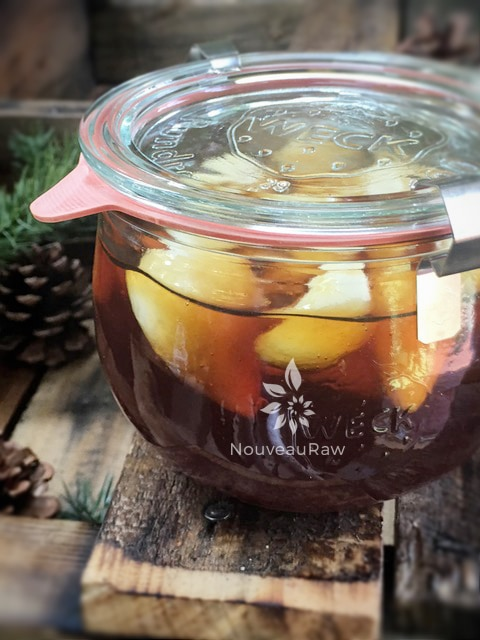 a close up of raw vegan Garlic Honey Throat, Cold and Flu Remedy displayed on barn wood in a sealed jar