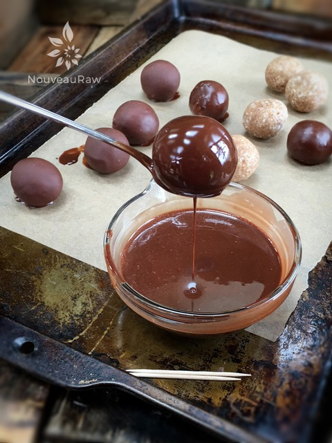 lifting the raw vegan Chocolate Covered Salted Caramel Macaroon out of the chocolate