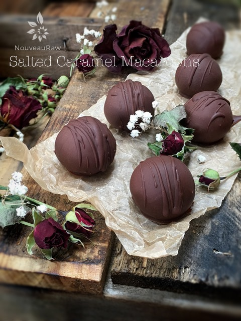 Chocolate Covered Salted Caramel Macaroons displayed on a wooden table and dried red roses