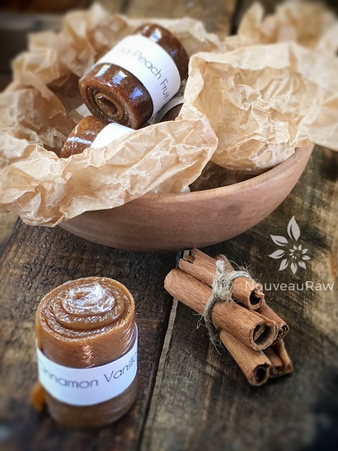 Cinnamon Vanilla Peach Fruit Leather rolled up and presented in a wooden bowl and cinnamon sticks