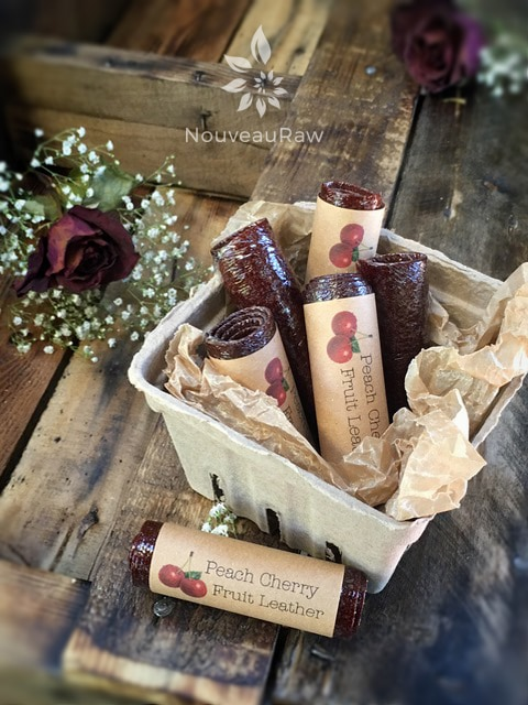 a container of raw  peach cherry fruit leather rolled and labels beautifully