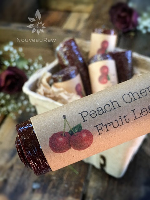 a close up of raw  peach cherry fruit leather rolled and labels beautifully