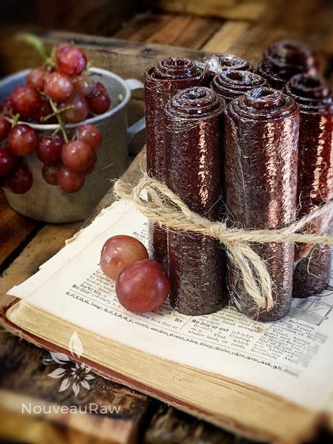 Raw, Vegan, Gluten free grape fruit leather rolled up and displayed on an antique dictionary