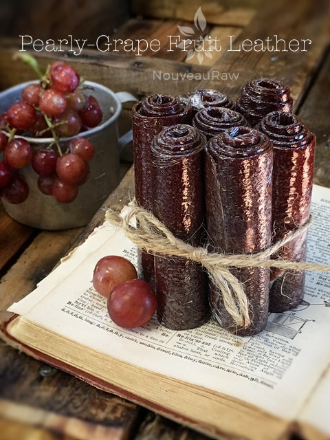 Raw, Vegan, Gluten free grape fruit leather rolled up and displayed on an antique dictionary and with grapes