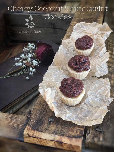 mouthwatering raw, gluten-free Cherry Coconut Thumbprints displayed on parchment paper