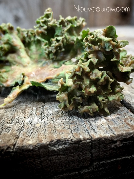 a close up raw vegan gluten-free Gingerbread Kale Chips photos on barn wood