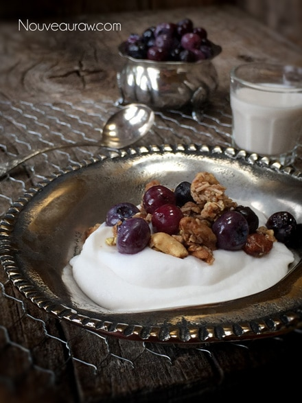 Raw creamy young Thai coconut yogurt fresh fruit and gronola in a silver bowl
