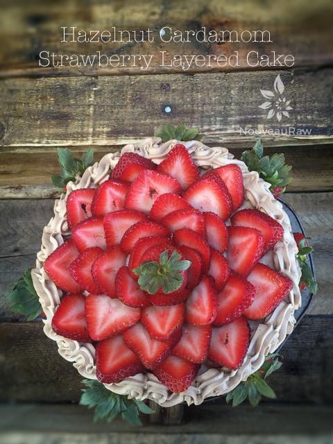 Beautifully decorated with fresh organic strawberries Raw Hazelnut Cardamom and Strawberry Layered Cake, so gorgeous so tasty