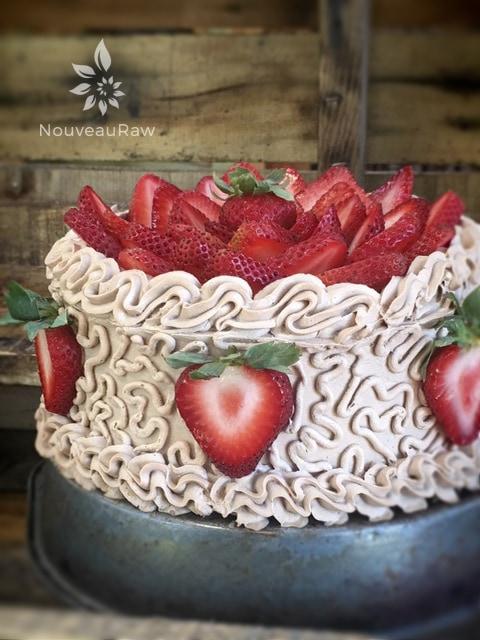 Master Piece, Raw Gluten-Free Hazelnut Cardamom and Strawberry Layered Cake decorated with fresh organic strawberries