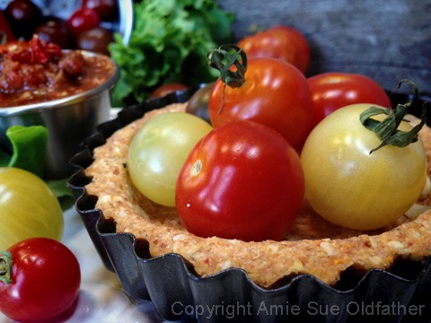 a close up of gluten free Sun-Dried Tomato and Basil Tart Crusts filled with cherry tomatoes