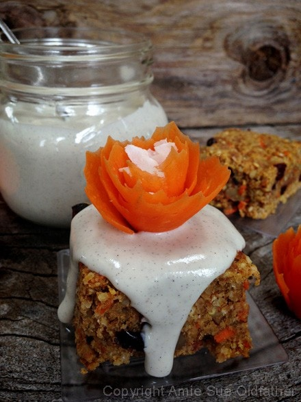 Raw Gluten-Free Buttery Walnut Carrot Cake Bars with vanilla bean icing, sprinkled shredded coconut in the center