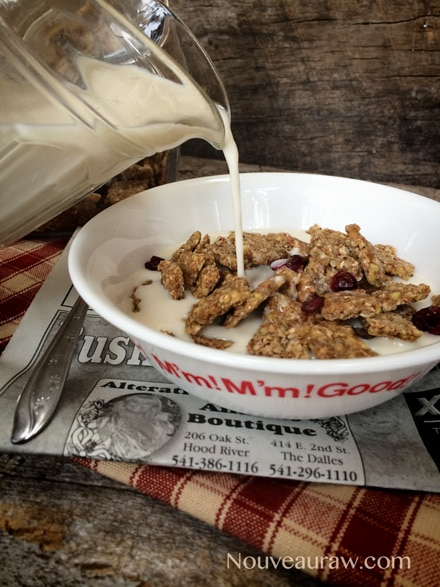 Adding nut milk to a bowl of Raw Almond Butter Cereal Crunch, sprinkled with dried cranberries