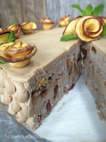 Delicious Raw Layered Apple Raisin Cake with Maple Cinnamon Frosting Decorating the top with the apple roses and mint leaves
