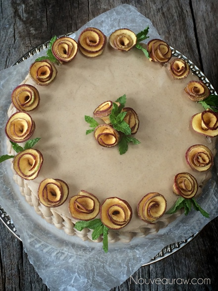 Beautifully Displayed Raw Layered Apple Raisin Cake with Maple Cinnamon Frosting Decorating the top with the apple roses and mint leaves