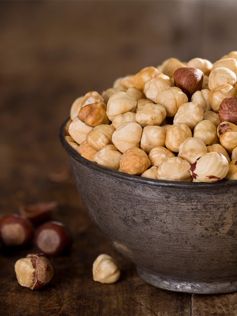 close up of raw hazelnuts in bowl