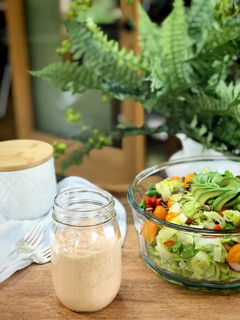Russian-Salad-Dressing on a wooden table with a fresh salad