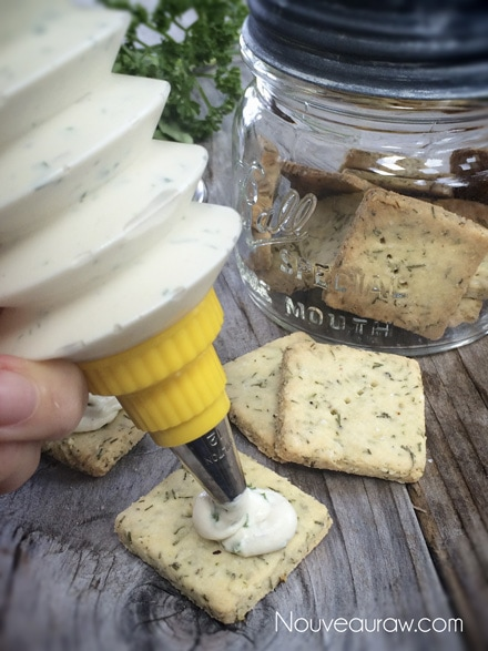 raw vegan Herbed Cashew Cheese being squeezed on crackers