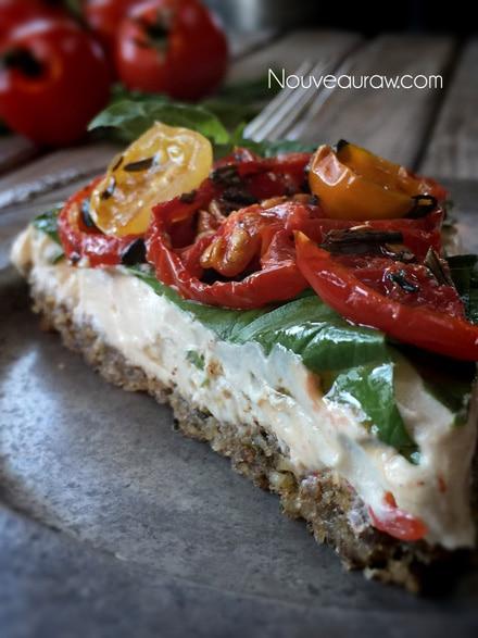 a close up single piece raw vegan 'Caprese' Herb and Tomato Tart