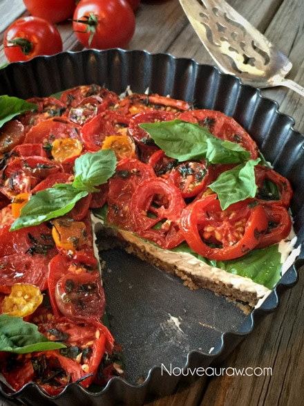 a piece removed from the raw vegan 'Caprese' Herb and Tomato Tart