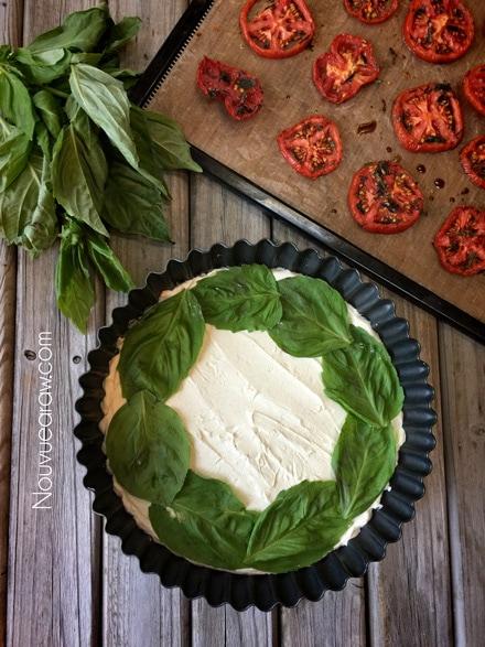 adding fresh basil leaves to the raw vegan Caprese Herb and Tomato Tart