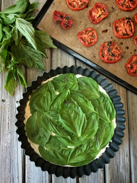 adding fresh basil leaves to the raw vegan Caprese Herb and Tomato Tart displayed on a wooden table
