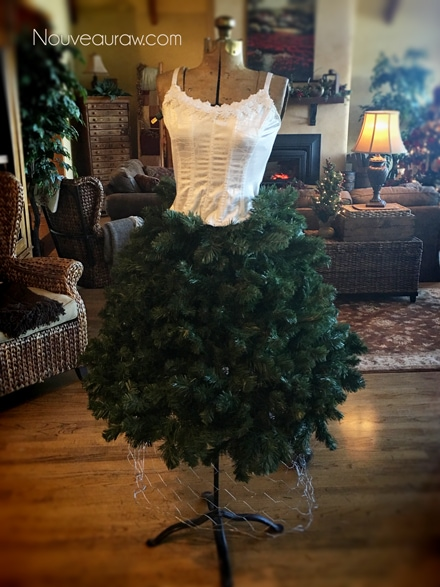 adding Christmas garland to the  the antique dress form to create a skirt