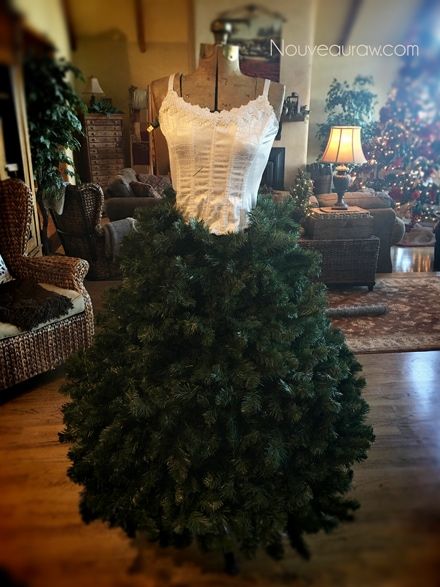 adding Christmas garland all the way to the floor to the the antique dress form to create a skirt