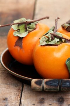 persimmons on a wooden table